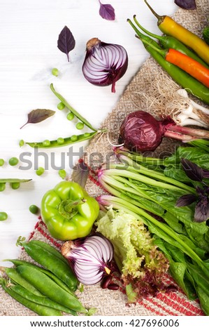 Fresh juicy vegetables such as hot pepper, purple onion, young peas, peppers and spinach on a white wooden background. Vegan concept. Fresh farm products