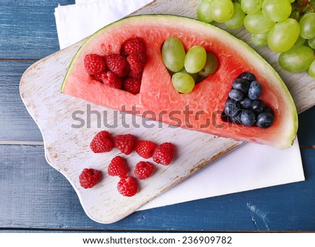 Fresh juicy watermelon slice  with cut out heart shape, filled fresh berries, on cutting board, on color wooden background - stock photo