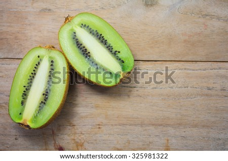 Fresh kiwi fruits on wooden table - stock photo