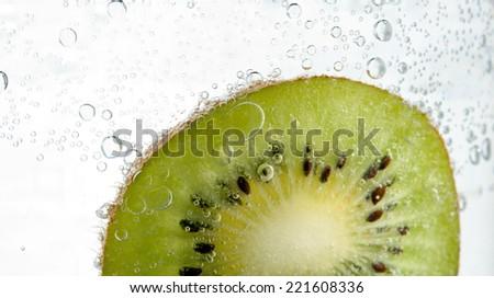 fresh kiwi is in water bubbles - stock photo