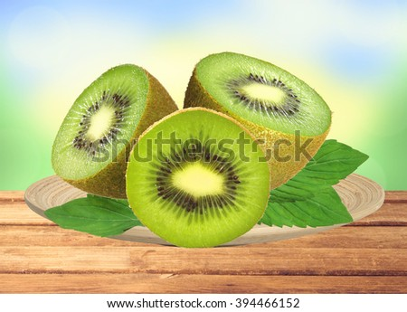 fresh kiwi on wooden plate on table over nature background