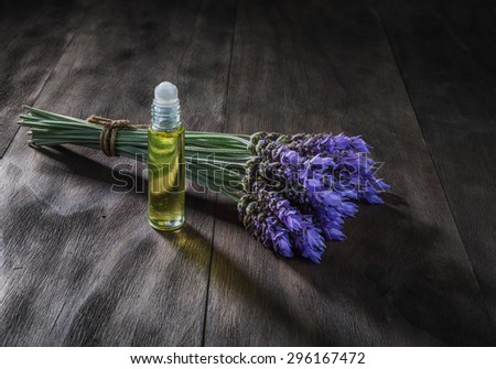 fresh lavender flowers and essential oil as natural aromatherapy for headache and migraine relief on old wooden background - stock photo