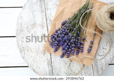 Fresh lavender with rope on parchment on wooden table, closeup - stock photo