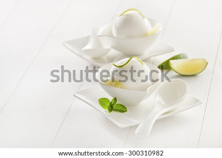 Fresh lemon and lime ice cream in a white cup. - stock photo