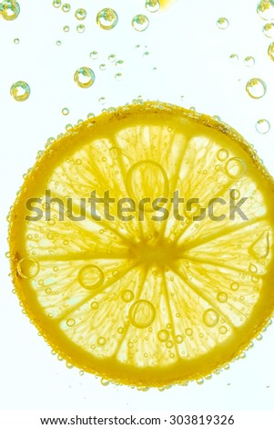 Fresh lemon slice in water with bubbles on white background - stock photo