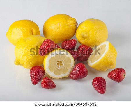 fresh lemon with strawberries on a white background - stock photo