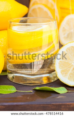 fresh Lemonade in jar and glass with yellow lemon on wooden kitchen background