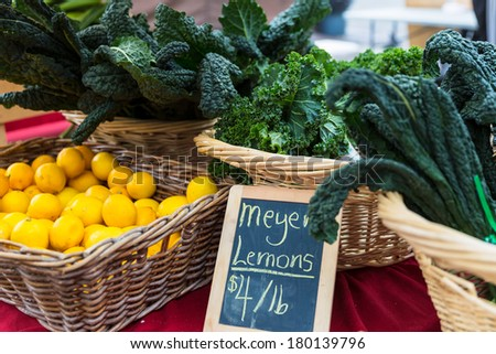 Fresh lemons and kale on display in baskets at a farmers market. Concept for farm to table. - stock photo
