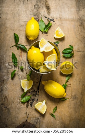 Fresh lemons in a bucket of leaves. On a wooden table. Top view - stock photo