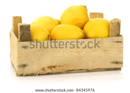fresh lemons in a wooden box on a white background