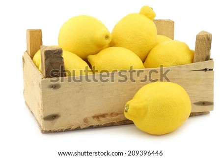 fresh lemons in a wooden crate on a white background