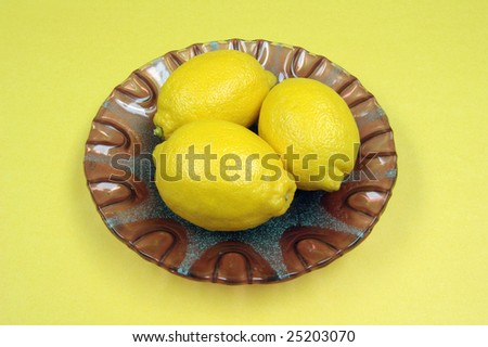 Fresh lemons on decorative purple plate with yellow background