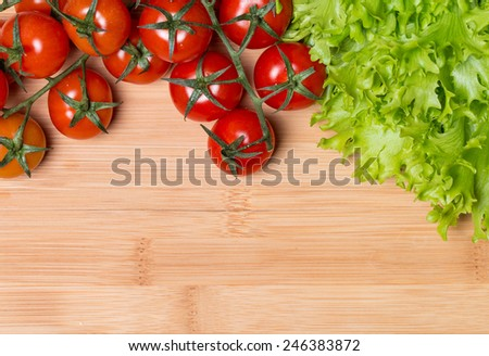 Fresh lettuce and tomatoes on wooden background - stock photo