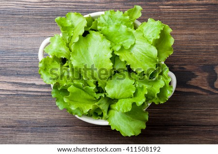 Fresh lettuce in a bowl on wooden rustic background. Cooking salad. Healthy food background. Top view - stock photo