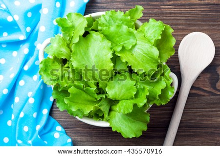 Fresh lettuce in a bowl on wooden rustic background. Cooking salad. Vegetarian food. Healthy food background. Top view - stock photo