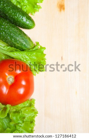 fresh lettuce salad, tomato and cucumber on wood table