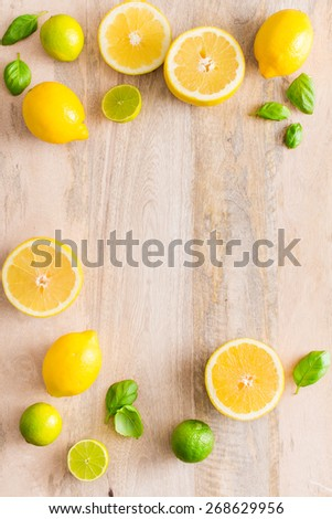 Fresh lime and lemon citrus fruits on wooden background. Copy and paste your own text. Empty space next to yellow and green juicy fruits on warm wooden bakground. - stock photo
