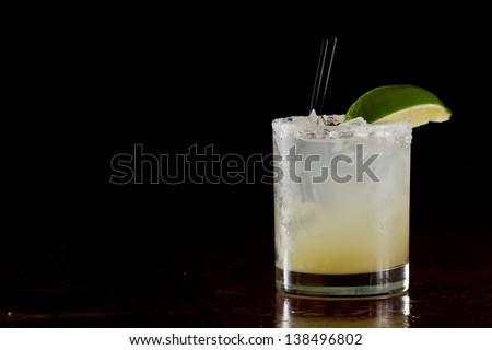 fresh lime juice margarita served on the rocks in a dark restaurant - stock photo