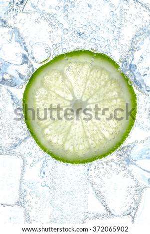 fresh lime slice and ice cubes in soda - stock photo