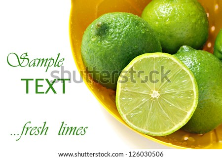 Fresh limes in yellow colander with water droplets on white background with copy space.  Macro with shallow dof. - stock photo