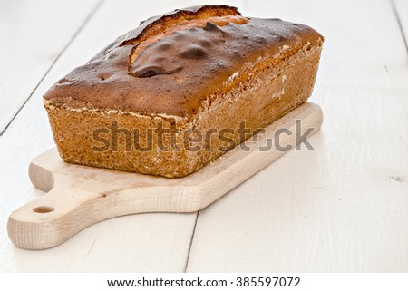 Fresh loaf cake on small wooden board and white wood table - stock photo