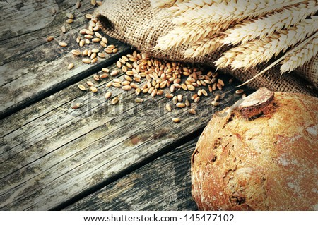 Fresh loaf of bread and wheat on wooden table