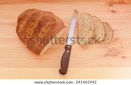 Fresh loaf of bread with a sharp knife and three cut slices on a pine table - stock photo