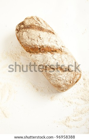 Fresh loaf of bread with flour, seen from above - stock photo