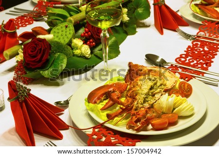 Fresh lobster and white wine on a festive table with red folded napkins - stock photo