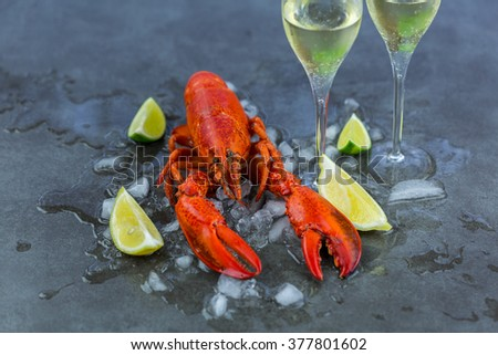 Fresh Lobster Chilling on Ice with Wedges of Lime and Two Glasses of Celebratory Sparkling Wine or Champagne - Still Life of Celebratory Lobster Dinner with Wine - stock photo