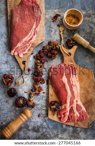 Fresh local meat concept.  Beef steak and fillet over on vintage cutting boards with rustic kitchen tools. - stock photo