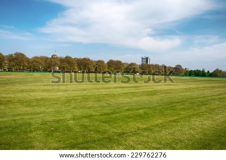 Fresh Look Grassy Landscape in Panorama View with Green Trees Afar on Lighter Blue And White Sky Above. - stock photo