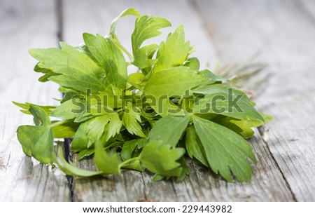 Fresh Lovage (detailed close-up shot) on wooden background - stock photo