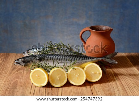 Fresh mackerel fish on the plate and sliced lemons on the table - stock photo