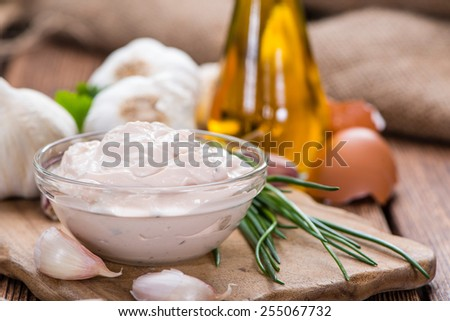 Fresh made Aioli (Garlic dip) on wooden background - stock photo