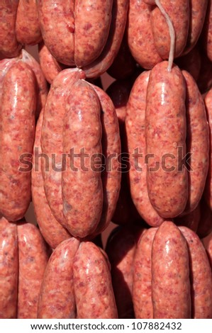Fresh made beef sausages hanging at a meat market - stock photo