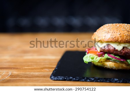 Fresh made cheeseburger with tomato, lettuce and onion. - stock photo