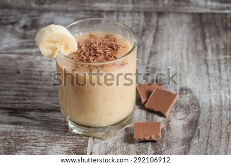 Fresh Made Chocolate Banana Smoothie on a wooden table. Selective focus. Milkshake. Protein diet. Healthy food concept. - stock photo