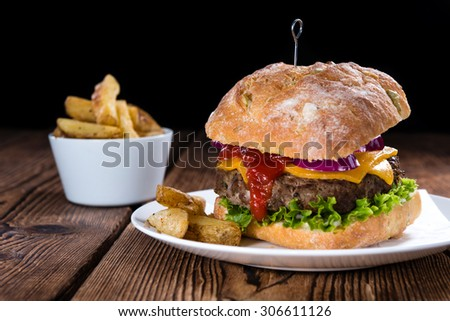 Fresh made Ciabatta Burger with chips on vintage wooden background - stock photo