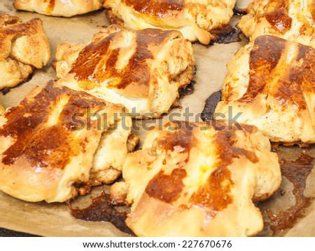 Fresh made cinnamon buns plaited on baking paper - stock photo