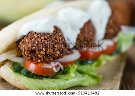 Fresh made Falafel Sandwich (close-up shot; selective focus) on an old wooden table