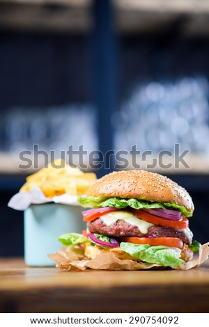 Fresh made hamburger with tomato, lettuce, onion and a pile of fries. - stock photo