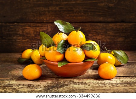 fresh mandarin oranges fruit with leaves on wooden table - stock photo