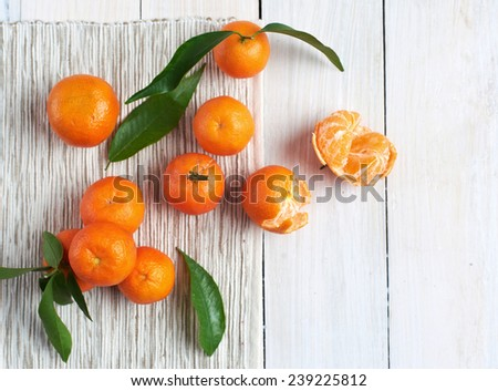 fresh mandarins with leafs on white wooden table - stock photo