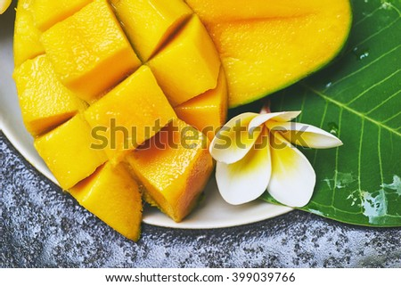 fresh mango in the plate on a wooden table with tropical background. Soft focus. - stock photo