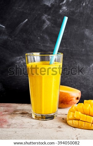 Fresh mango smoothie on a rustic counter served with a halved fresh fruit on the pip and decorative hedgehog cut portion in the foreground for a healthy tropical summer drink - stock photo