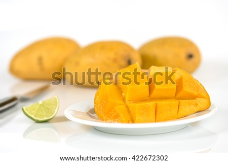 Fresh mango with mango already peeled and cut mango on a white plate with mango blurred in the background. Mango is sliced into small pieces of mango on a white plate and a knife beside the mango. - stock photo
