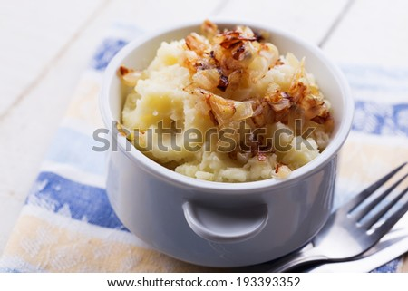 Fresh mashed potatoes in white bowl with fried onion on wooden background. Selective focus. - stock photo