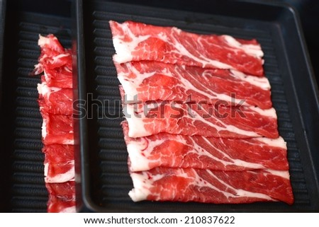 Fresh meat sliced and served on tray for Japanese Sukiyaki - stock photo