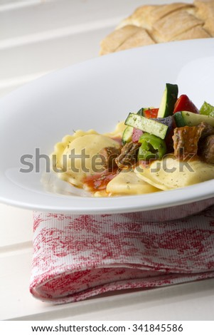 fresh meat tortellini with tomato and sauteed vegetables on red and white tablecloth